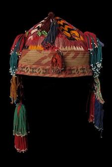 Kleurrijke traditionele aziatische kalotje hoed met staartjes op een donkere achtergrond