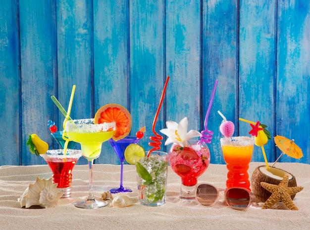 Kleurrijke tropische cocktails op strand op blauwe houten muur