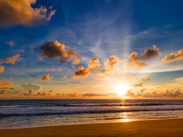 Kleurrijke tropische strandzonsondergang met gele, blauwe hemel en zonnestraal. zonsondergang over zee op het strand van phuket, thailand.