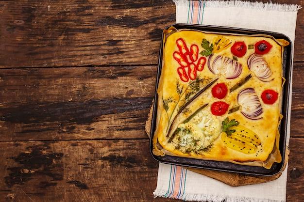 Kleurrijke tuin focaccia. verse rijpe groenten, olijfolie, groenen. traditionele italiaanse bakkerij