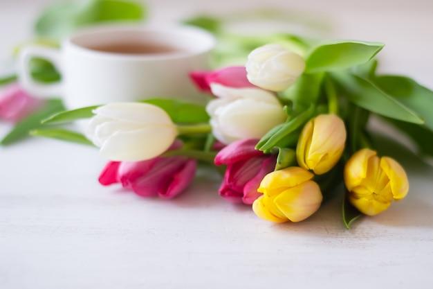 Kleurrijke tulpen en kopje thee op de witte houten tafel