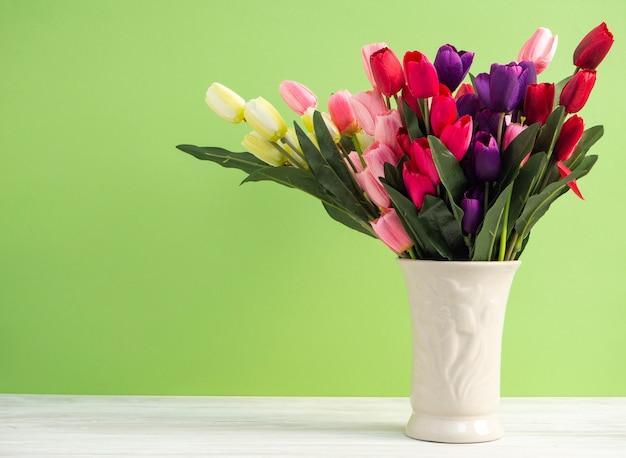 Kleurrijke tulpen in vaas op de witte groene achtergrond van de lijstmuur