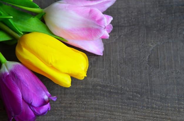 Kleurrijke tulpen op oude houten tafel. lente tulp bloemen voor moederdag