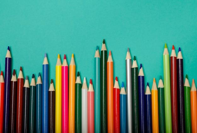 Kleurrijke veelkleurige potloden die in een golf over blauwe achtergrond worden geschikt