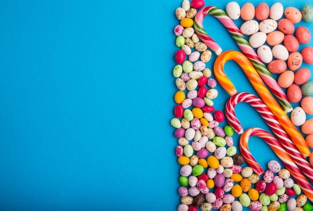 Kleurrijke veelkleurige snoepjes op een blauwe achtergrond. kopieer ruimte, bovenaanzicht.