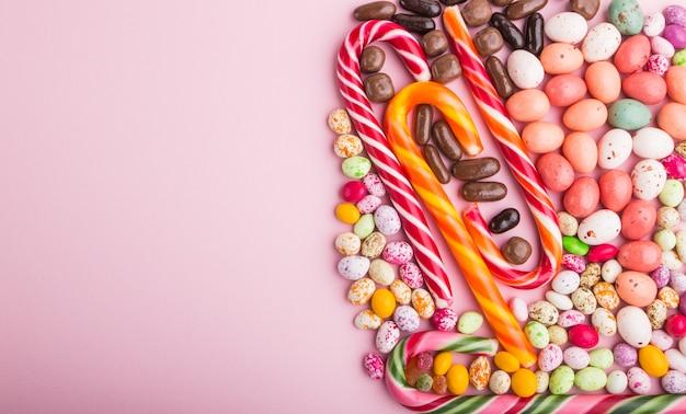 Kleurrijke veelkleurige snoepjes op een roze pastel achtergrond. kopieer ruimte, bovenaanzicht.