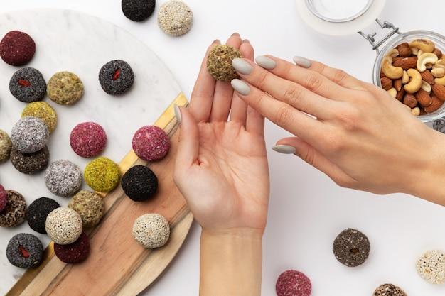 Kleurrijke vegan snoepjes energie ballen op een bord met dames hand geïsoleerd