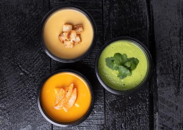 Kleurrijke veganistische roomsoep in zwarte voedseldozen, plat leggen. evenwichtige voeding concept. voedsellevering