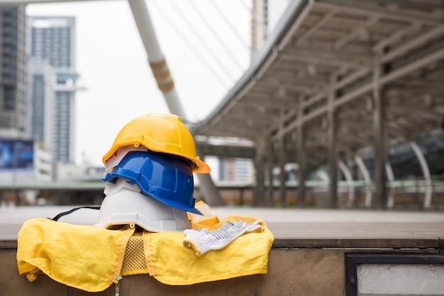 Kleurrijke veiligheidshelmen, handschoenen en gele arbeiderskleding op voetpad met vage moderne stadsachtergrond. techniek en bouwmateriaal. ingenieur zware industrie project in de stad.