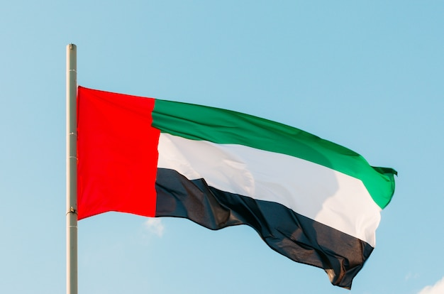Kleurrijke verenigde arabische emiraten vlag zwaaien op blauwe hemel.
