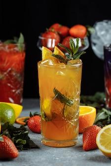 Kleurrijke verfrissende drankjes voor de zomer, koud aardbeienlimonadesap met ijsblokjes in de glazen gegarneerd met gesneden verse citroenen.