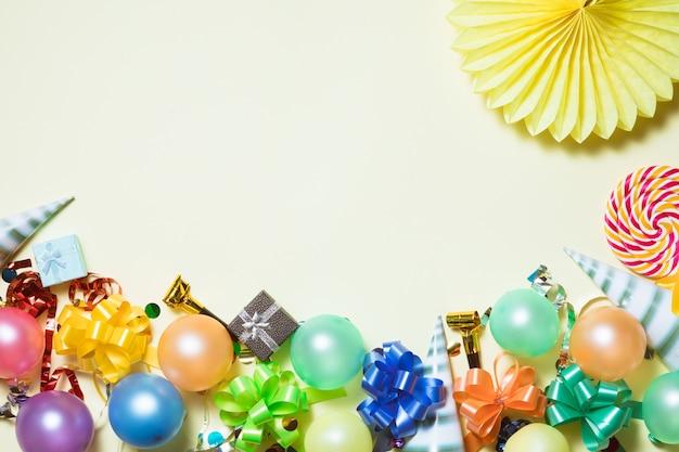 Kleurrijke verjaardag partij achtergrond met feestmutsen en confetti op gele achtergrond