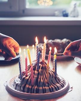 Kleurrijke verjaardagstaart met met handen die de partij van het negentien kaarsenhuis branden