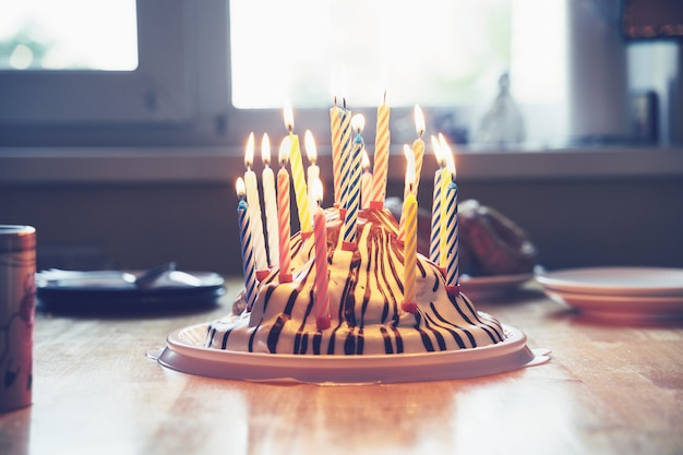 Kleurrijke verjaardagstaart met negentien kaarsen op tafel kinderlijke home party