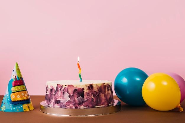 Kleurrijke verlichte kaars op verjaardagscake met feesthoed en ballons op bureau tegen roze achtergrond