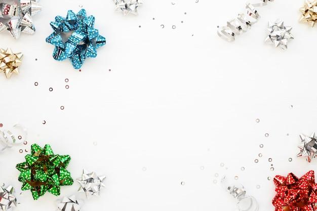Kleurrijke verpakking pull bogen en confetti op wit oppervlak