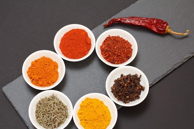 Kleurrijke verschillende gemalen kruiden, saffraan, karwij, curry, droge rozemarijn en kruidnagel in porseleinen kommen op zwarte stenen snijplank met droge rode peper. bovenaanzicht.