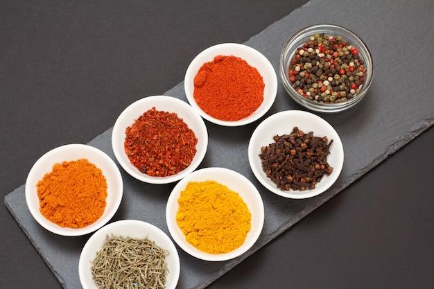 Kleurrijke verschillende gemalen specerijen, droge kruidnagel en kruiden in kommen op zwarte stenen snijplank. bovenaanzicht.