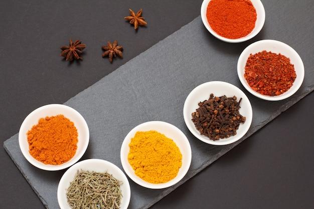 Kleurrijke verschillende gemalen specerijen, droge kruidnagel en kruiden in porseleinen kommen op stenen snijplank. bovenaanzicht.