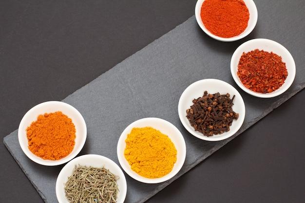 Kleurrijke verschillende gemalen specerijen, droge kruidnagel en kruiden in porseleinen kommen op stenen snijplank en zwarte achtergrond. bovenaanzicht.