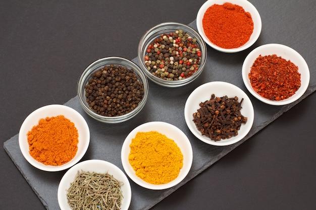 Kleurrijke verschillende gemalen specerijen, droge kruidnagel en kruiden in porseleinen kommen op zwart stenen bord. bovenaanzicht.