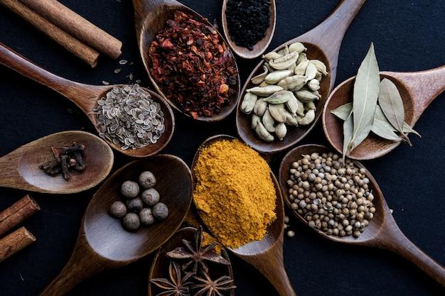 Kleurrijke verschillende kruiden en specerijen voor het koken op een donkere achtergrond.