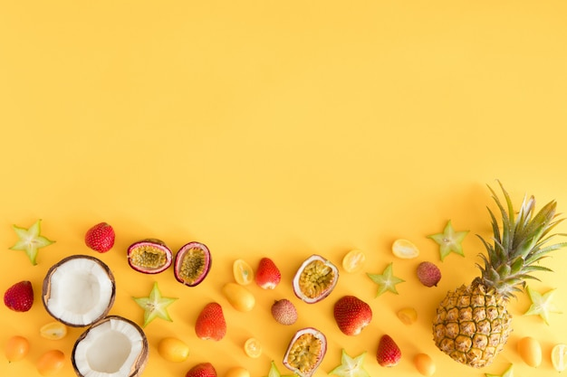 Kleurrijke verse exotische vruchten op pastel gele tafel.