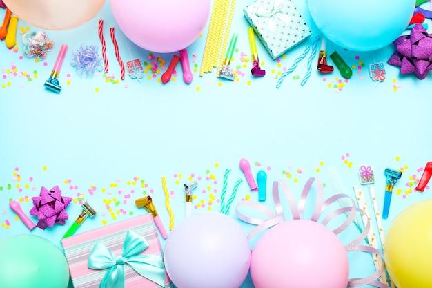 Kleurrijke viering met verschillende partij confetti, ballonnen, geschenken en decoratie op blauw. Premium Foto