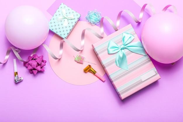 Kleurrijke viering met verschillende partij confetti, ballonnen, geschenken en decoratie op roze.