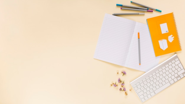 Kleurrijke viltstiften; bloem; notitieboekje met toetsenbord over gekleurde achtergrond