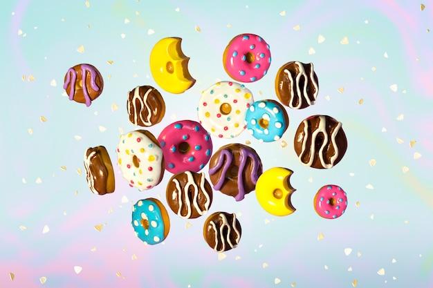 Kleurrijke vliegende donuts met gouden lovertjes op lichte holografische