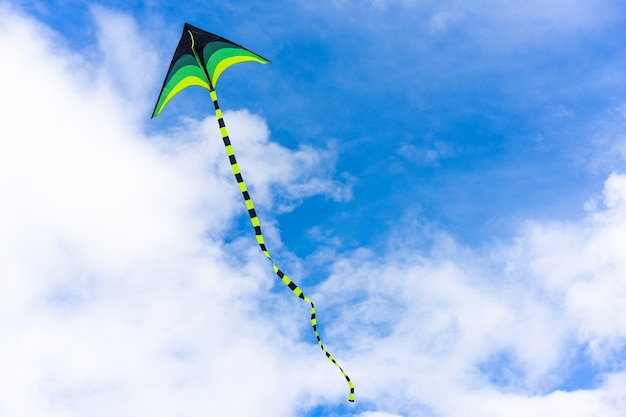 Kleurrijke vlieger die door lucht op hemel vliegt