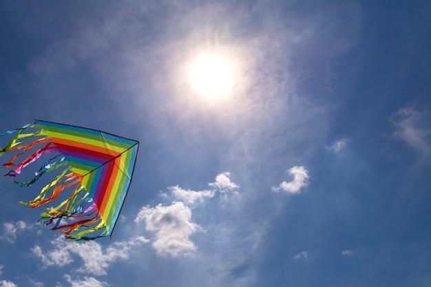 Kleurrijke vlieger die in blauwe hemel hemel als achtergrond vliegt. felle zon