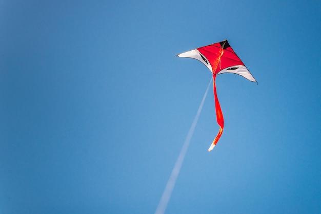 Kleurrijke vlieger die in de blauwe hemel vliegt
