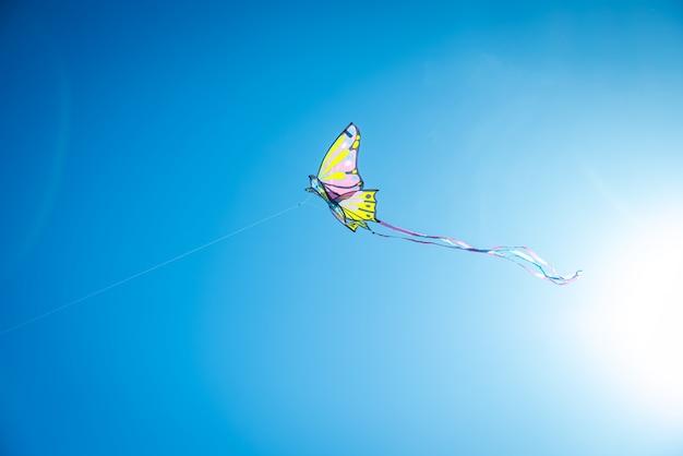 Kleurrijke vlieger met lange staart die in de blauwe hemel tegen de zon vliegen, exemplaarruimte.
