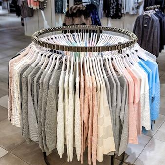 Kleurrijke vrouwelijke kleding op kleerhangers in een winkel