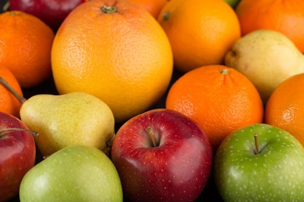 Kleurrijke vruchten bos van verschillende vruchten zoals appels en sinaasappelen op grijze bureau