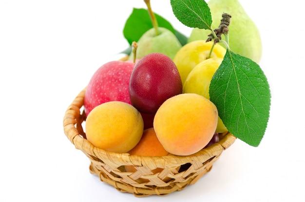 Kleurrijke vruchten in een rieten mand. geïsoleerd