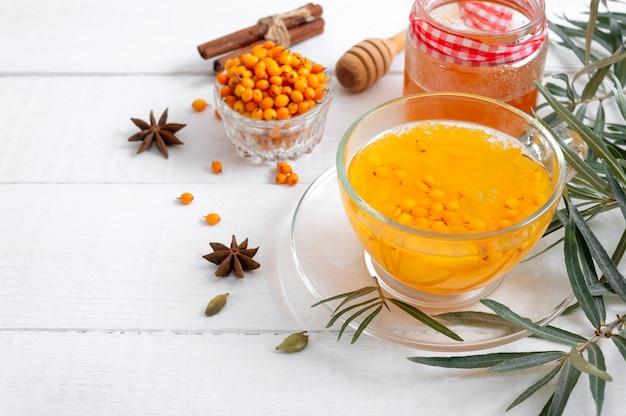 Kleurrijke warme natuurlijke duindoornthee in een glazen beker concept van warme seizoensgebonden dranken
