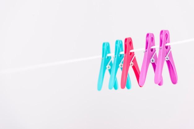 Kleurrijke wasknijpers die op waslijn hangen