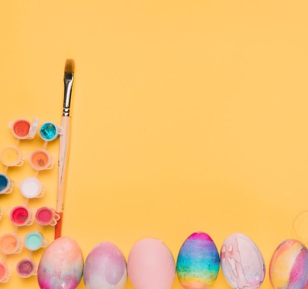 Kleurrijke waterverfverf met penseel en paaseieren op gele achtergrond met ruimte voor het schrijven van de tekst