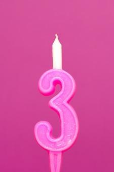Kleurrijke wax verjaardagskaars op roze