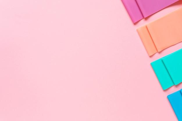 Kleurrijke weerstandsbanden op roze achtergrond kopie ruimte fitnessapparatuur tools