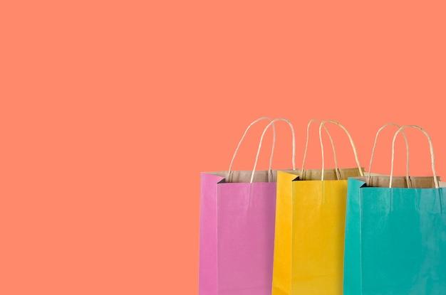 Kleurrijke winkelen papieren zakken op roze achtergrond.