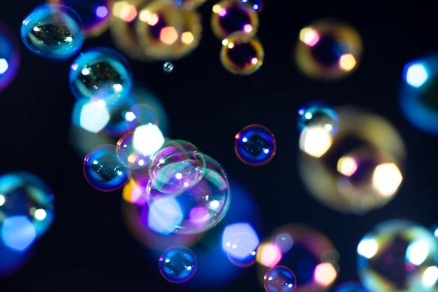 Kleurrijke zeepbellen zweven in het donker