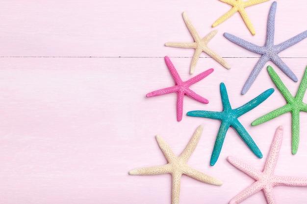Kleurrijke zeester op roze houten achtergrond
