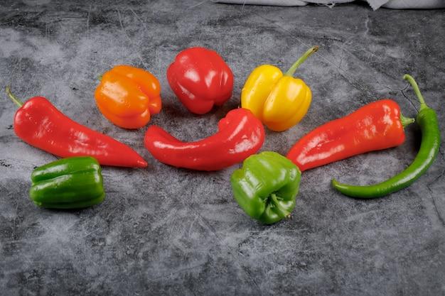 Kleurrijke zoete en chili pepers op het grijze marmer.