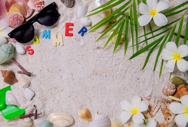 Kleurrijke zomer tekst met schelpen en plumeria bloemen op zand