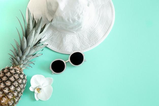 Kleurrijke zomer vrouwelijke mode-outfit plat leggen. witte stijlvolle dameshoed met zonnebril en verse ananas. zomer mode of vakantie reizen concept