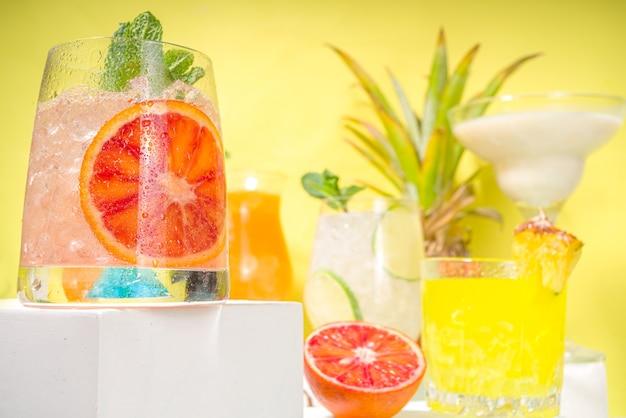 Kleurrijke zomerdranken set. diverse heldere alcoholische cocktails en dranken, in verschillende glazen, met tropisch fruit